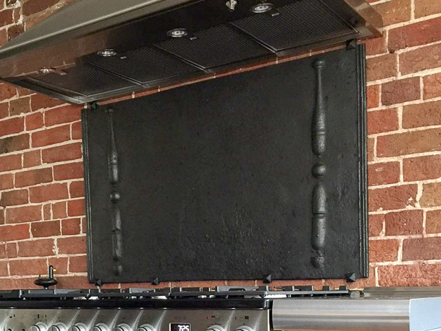 Haardplaat opgehangen aan de muur met montagebeugels